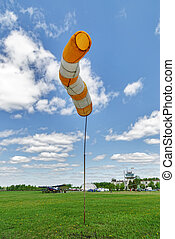Airport windsock on blue sky background in windy weather indicate the local wind direction. Also called: air sock, drogue, wind sleeve, wind cone