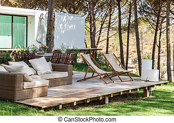 Summer house deck with chairs and sofa