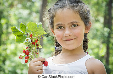 Summer in the forest on a bright sunny afternoon, a little girl, is holding strawberries in her hands.
