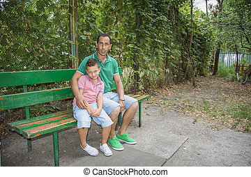 Summer in the street on the bench is a son with his father.