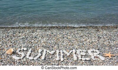 SUMMER inscription from stones in pebble beach with sea surf
