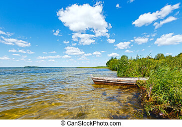 Summer lake view with wooden boat.