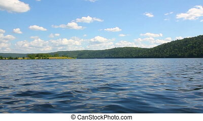 summer lake with waves under blue sky