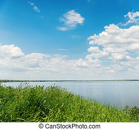 summer landscape with green grass, river and clouds in blue sky