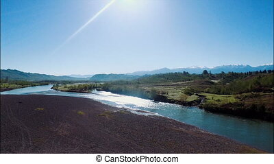 Summer landscape with river, field and blue sky