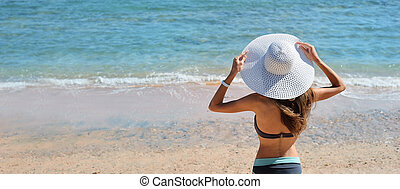 Summer lifestyle portrait of pretty young suntanned woman in big white hat. Looking at the sea. Enjoying life on beach, time to travel. Panoramic banner