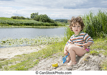 Summer little curly girl playing with a shovel on the riverbank.