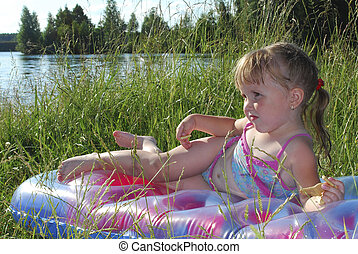 Summer little girl sunning at the lake in the grass