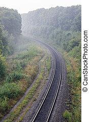 Summer morning landscape. Empty railroad turn in sunrise mist