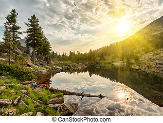 Summer morning over little lake. Sun rays shine between...