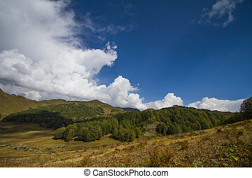 Summer mountain landscape with cumulus cloud on blue sky.