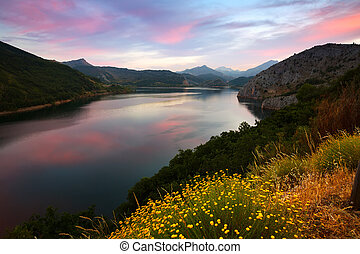 Summer mountains landscape with lake in sunset