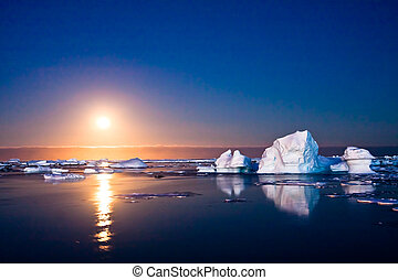Summer night in Antarctica. Icebergs floating in the ...