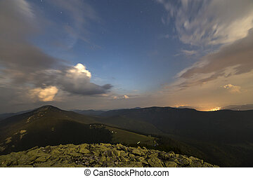 Summer night in mountains. Starry dark blue sky and white clouds at sunset over mountain range.