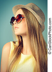 Close-up portrait of a beautiful girl in summer clothes and sunglasses.