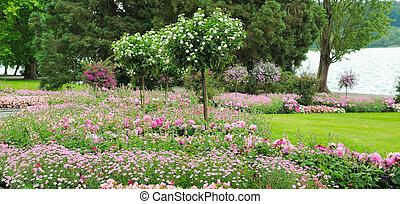 Summer park with lawn and flower garden. - Summer garden...