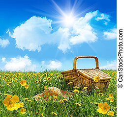 Summer picnic basket with straw hat in a field