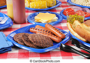 A picnic table with hamburgers, hot dogs, corn on the cob, and all the fixings