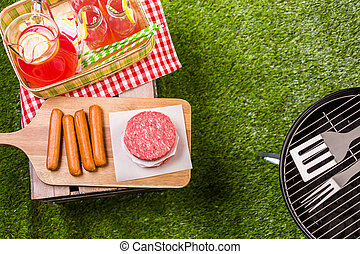 Summer picnic with small charcoal grill in the park.