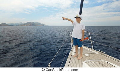 Summer picture. A happy boy in a cap is standing on the yacht and counting the number of yachts that went to sea. Racing of sailing yachts.