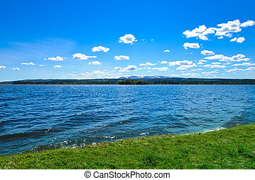 picture of lawn, lake, mountains and sky