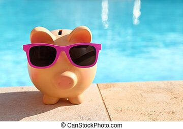 Summer piggy bank with sunglasses in front of a swimming...