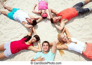 Six friends having rest on sandy beach