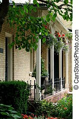 Summer Porch 02 - A covered porch with hanging baskets and...