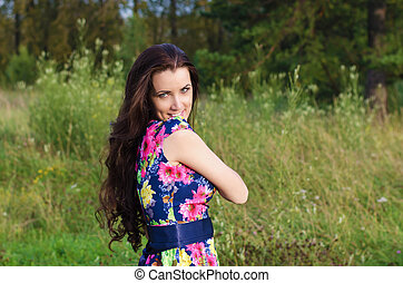 Summer portrait of a beautiful woman on nature background