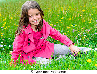 happy cute child sitting in a grass of a flower garden