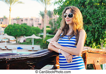 summer portrait of young attractive woman with sunglasses in resort