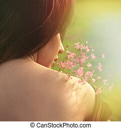 summer portrait of young woman with flower back shot closeup outdoors