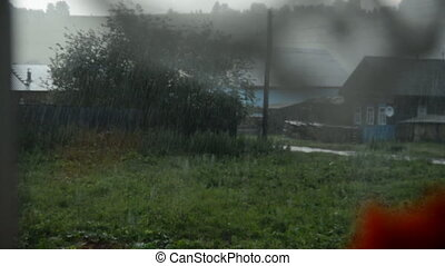 Summer rain. View of the village from the rain. The gloomy...