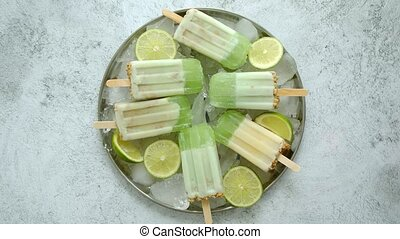 Summer refreshing homemade lime popsicles placed on metal tray with chipped ice over stone background, top view. Flat lay