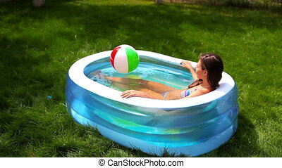 Summer relaxation - Lovely girl relaxing in a pool set in...