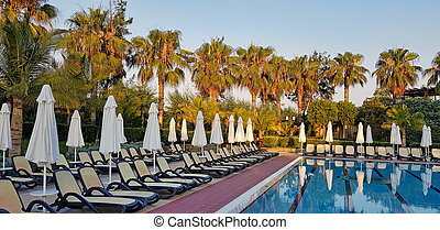 Summer resort: swimming pool and chaise loungues