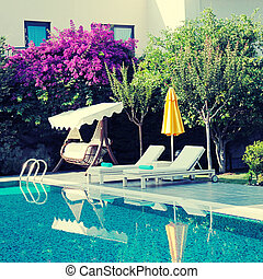 summer resort with outdoor furniture near the swimming pool