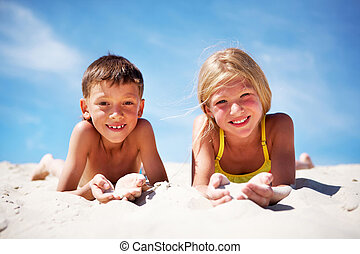 Summer rest - Photo of happy siblings lying on beach and...