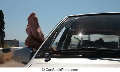 Summer road trip car vacation - Female feet hanging out of...