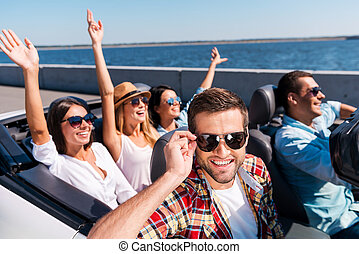 Summer road trip. Group of young happy people enjoying road trip in their convertible while handsome man adjusting his sunglasses and smiling