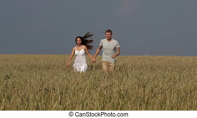 Summer runners - Happy rural couple running across the field...