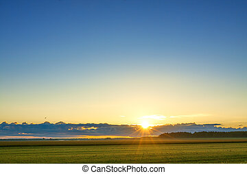 landscape with sunrise, field, sky and sun