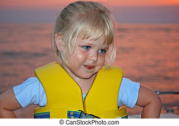 Summer Safety - Little girl wearing a life jacket at sunset.