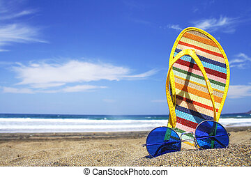 Sunglasses and beach shoes on the beach on a bright day