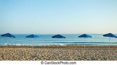 Summer sea beach background with blue umbrellas