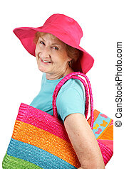A cute senior lady happy to be going to the beach. Isolated on white.