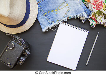 Summer set of women's clothes. Female blouse with denim shorts, hat, vintage camera and notebook. Top view. From above.