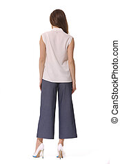 summer short sleeve shirt blouse high heels and culottes trousers on brunette indian woman back view