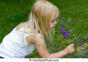 Little blond girl sniffing a purple flower.