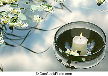 summer spa - white candle in glass floating in water...